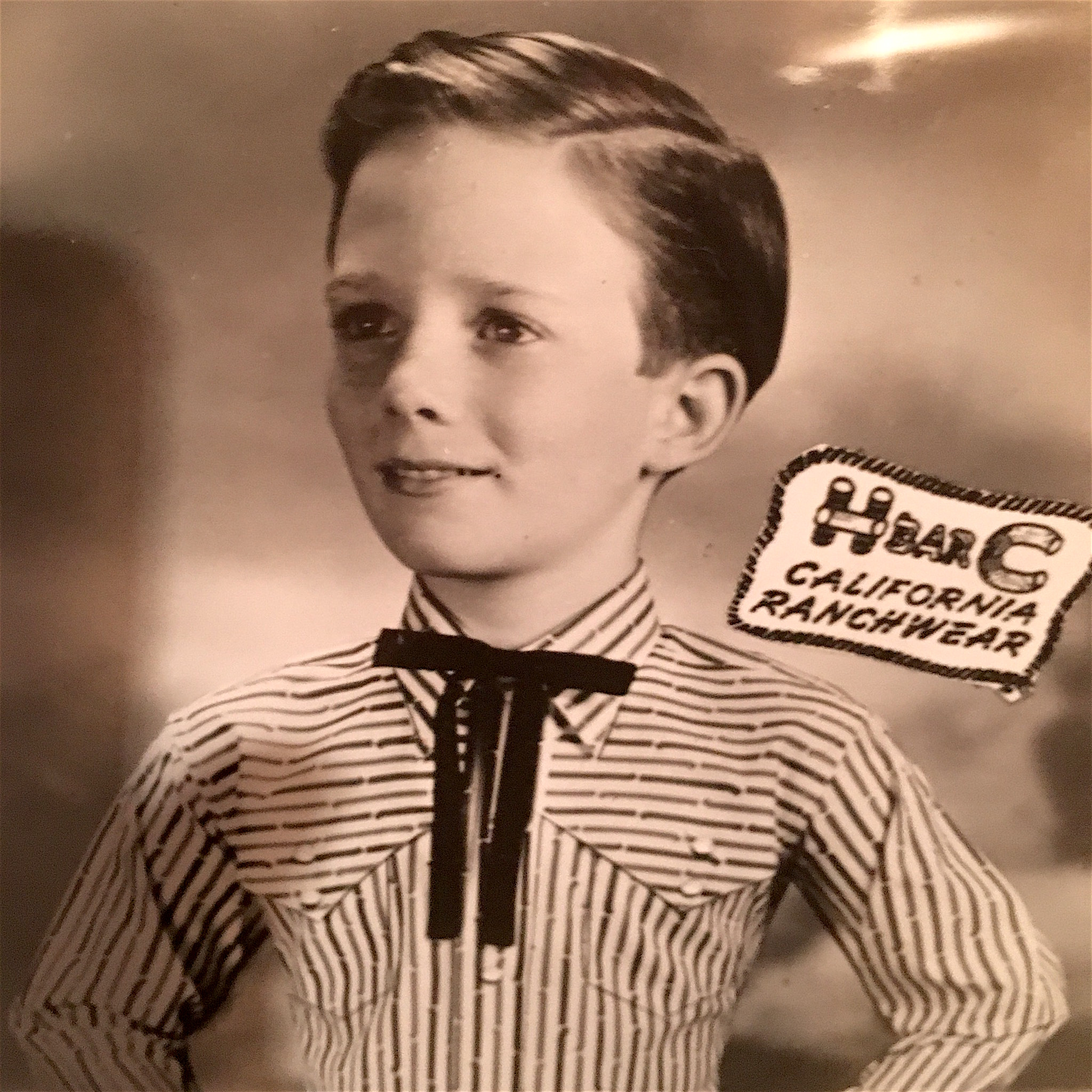 Child modeling in an H-Bar-C California Ranchwear shirt with a black string tie